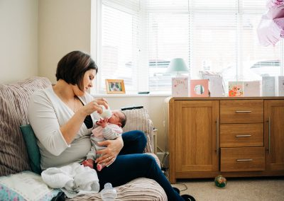 Mum bottle feeding baby on sofa
