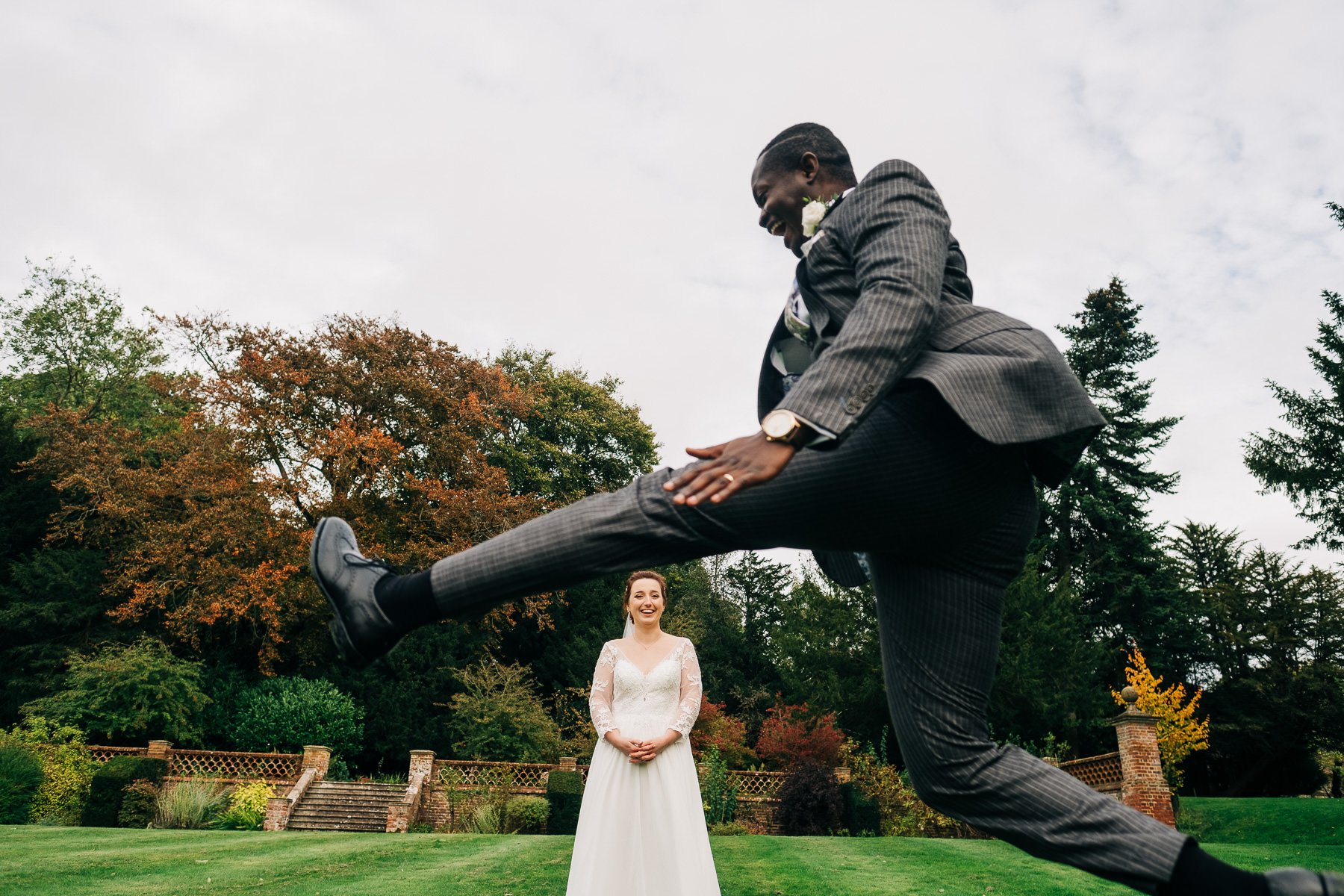 Groom jumping over bride